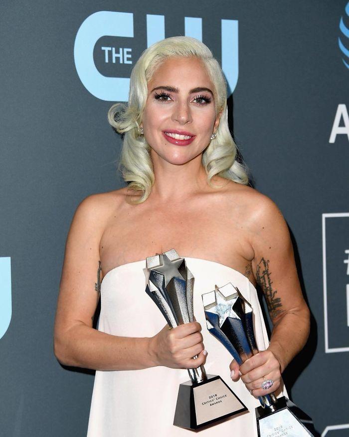 lady gaga holding two awards