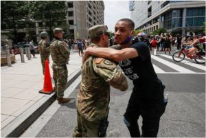 A demonstrator hugs a National Guard soldier during a protest
